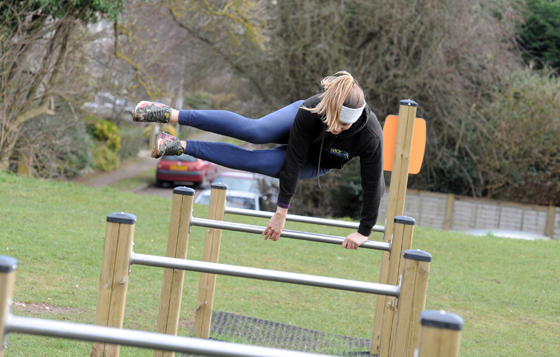 A park user jumps over an obstacle on a trim trail